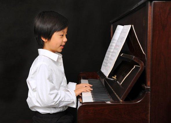 Китайский ребенок играет напианино