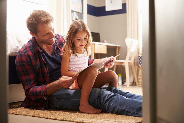 Отец с дочкой читают книгу