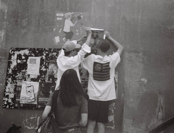 Александр Сапрыкин расклеивает плакаты сосвоими рисунками для бренда SRNK