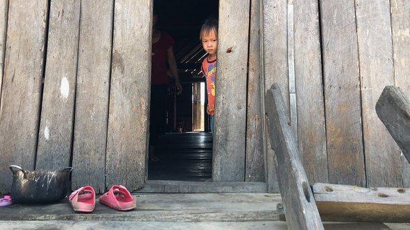 Малыш выглядывает издома. Деревня мнонгов, провинция Даклак