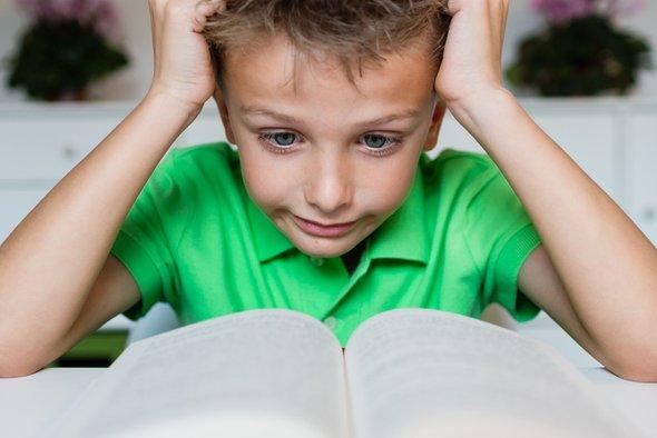 Ребёнок струдом читает книгу